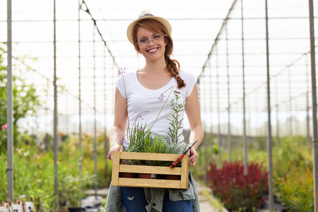Portrait of beautiful young woman holding wooden box with plants and flowers in the greenhouse Stock Photo