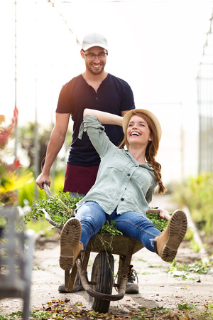Shot of happy couple smiling and have fun with a wheelbarrow in the greenhouse