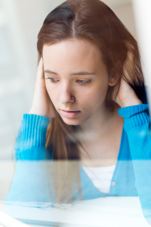 Portrait of depressed young woman sitting at home. Stock Photo