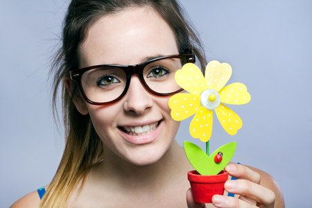 Portrait of beautiful young woman showing one artificial daisy