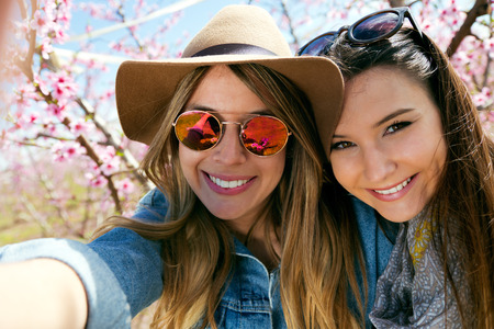 Portrait of two beautiful young women taking a selfie in the field. 写真素材