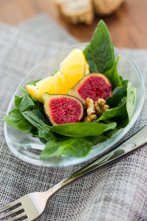 Portrait of salad with figs, nuts and orange.