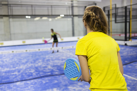 Portrait of two young women playing paddle tennis.
