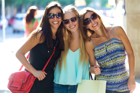 Outdoor portrait of group of beautiful young girls in the street. Shopping day.