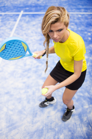 Portrait of beautiful young woman playing paddle tennis indoor.