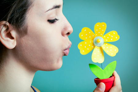 Portrait of beautiful young woman blowing on artificial daisy