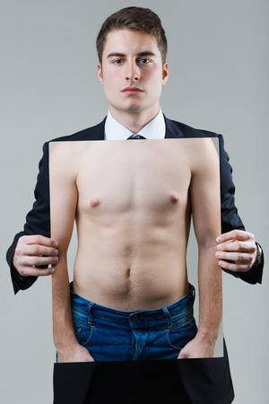 Portrait d'homme d'affaires en costume noir tenant une photo d'un torse masculin.