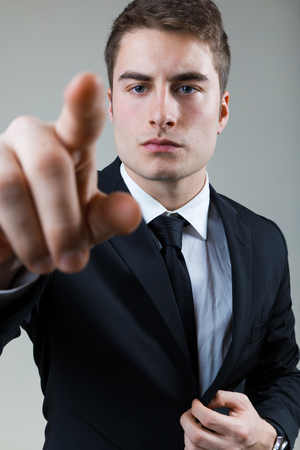 Portrait of business man with pointing to something or touching a screen. Archivio Fotografico - 111625460