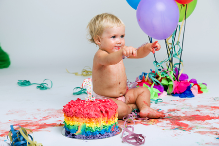 Portrait of baby girl celebrating her first bithday with gourmet cake and balloons.