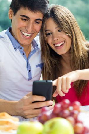 Portrait of couple using mobile phone on romantic picinic. Stock Photo