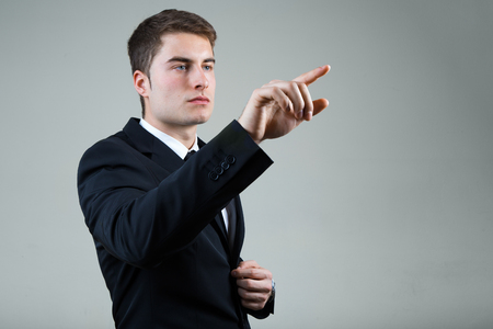 Portrait of business man with pointing to something or touching a screen.