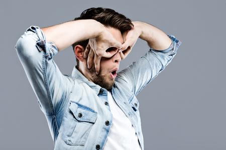 Portrait of handsome young man making finger glasses over gray background. Stok Fotoğraf