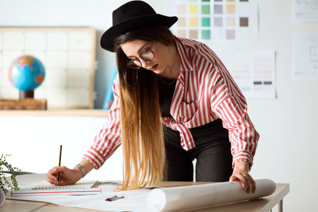 Shot of pretty young architect woman working on a blueprints in the office.