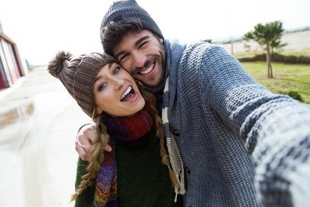 Porträt von schönen jungen Paaren mit Handy in einem kalten Winter am Strand.