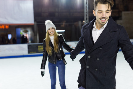 Portrait of beautiful young couple ice skating on rink outdoors.