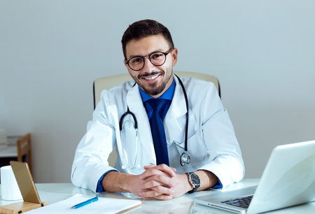 Portrait of confident male doctor smiling and looking at camera in the office. Stock Photo