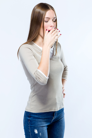 Portrait of beautiful young woman yawning over white background.