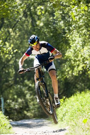 Portrait of handsome young man cycling in the mountain. Stockfoto - 111587803