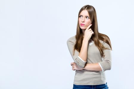 Retrato de mujer joven hermosa pensando sobre fondo blanco.