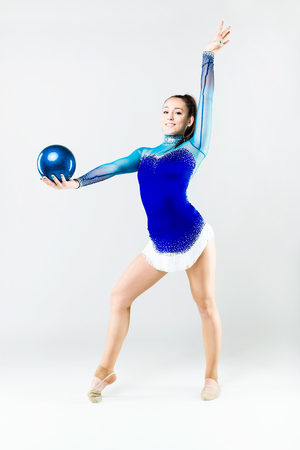 Portrait of beautiful gymnast athlete doing exercise with ball. Isolated on white.