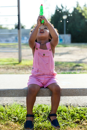 Portrait of a african american baby playing with water gun in the park. Imagens