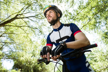 Portrait of handsome young man relaxing after cycling in the mountain. Stockfoto - 111587617