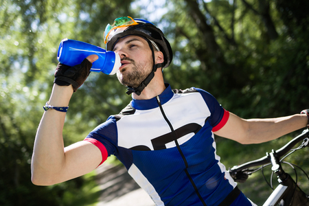 Portrait of handsome young man drinking water after cycling in the mountain.