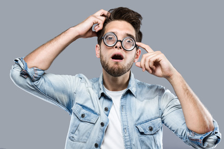 Portrait of handsome young man with funny glasses joking and making funny face over gray background.