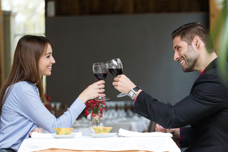 Portrait of beautiful young couple toasting wine glasses in the restaurant.