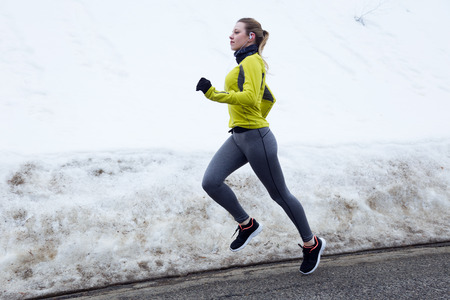 Outdoor portrait of young woman stretching and preparing for running on the road.