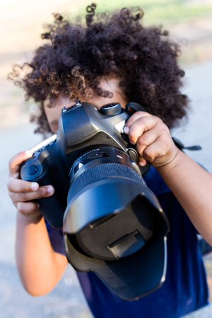 Portrait of a african american baby playing with professional camera in the park.