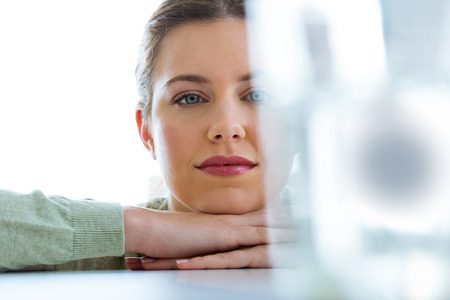 Portrait of beautiful young woman looking at a glass with an effervescent pill.