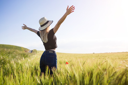 Portrait of beautiful young woman enjoying summer in a field. Stock Photo