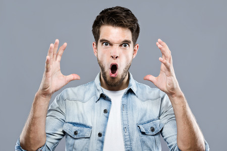Portrait of angry young man screaming over gray background.