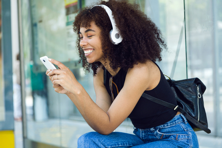 Outdoor portrait of beautiful young woman listening to music in city.