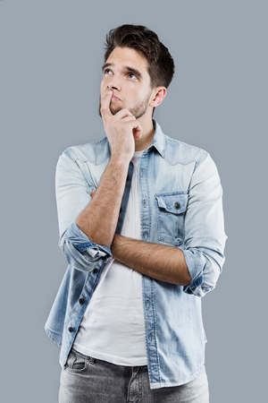Portrait of handsome young man thinking over gray background.
