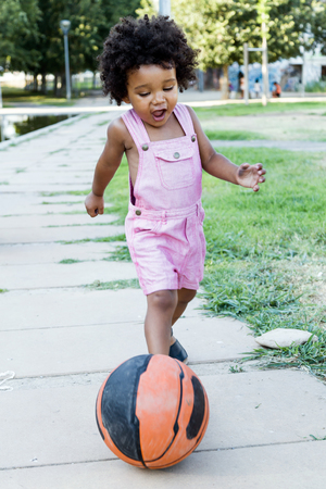 Portrait of a african american baby playing with ball in the park.