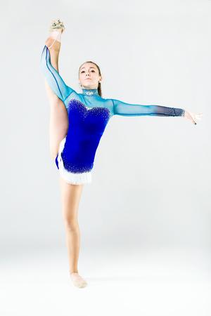 Portrait of beautiful gymnast athlete doing exercise. Isolated on white.