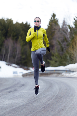 Outdoor portrait of pretty young woman running on the road.