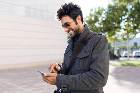 Portrait of modern young man using his mobile phone in the street.
