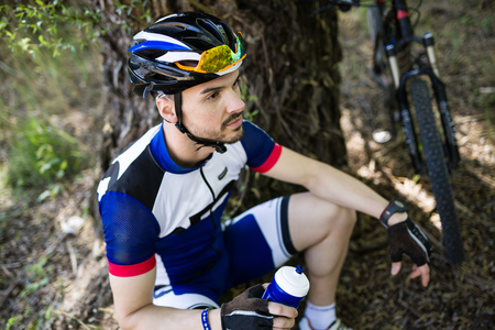 Portrait of handsome young man relaxing after cycling in the mountain. Stockfoto - 111526504
