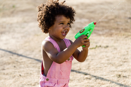Portrait of a african american baby playing with water gun in the park. 写真素材