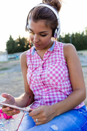 Portrait of beautiful young woman listening to music with digital tablet in the park. Banco de Imagens