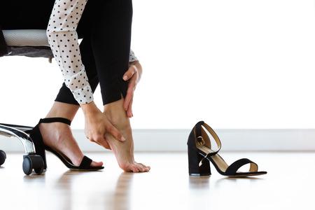 Primo piano di una donna d'affari seduta su una sedia e che si massaggia le dita dei piedi doloranti dopo aver indossato i tacchi ogni giorno.