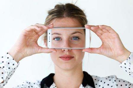 Portrait of beautiful young woman holding her mobile phone on her face with photo of herself isolated on white.