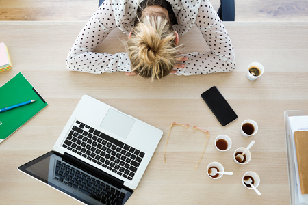 Shot of tired young businesswoman sleeping on her desk in the office.