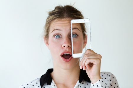 Portrait of surprised young woman holding her mobile phone on her face with photo of herself isolated on white. Stockfoto