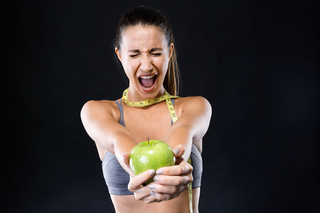 Portrait of angry young woman with a tape measure around her neck and holding an apple over black background. Stock Photo