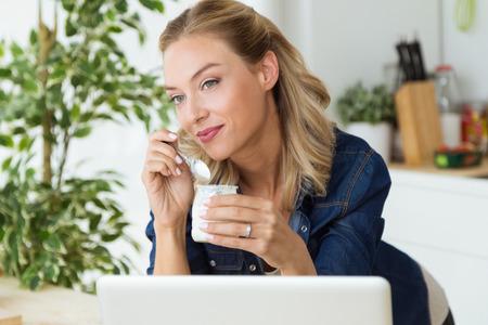 Retrato de joven y bella mujer comiendo yogur en casa.