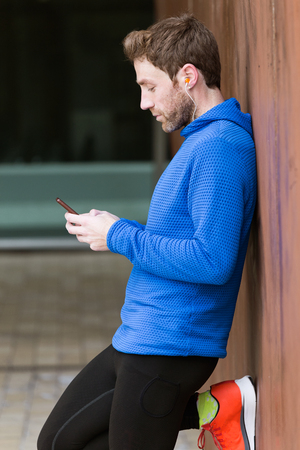 Portrait of sporty young man using his mobile phone in the street. Stockfoto